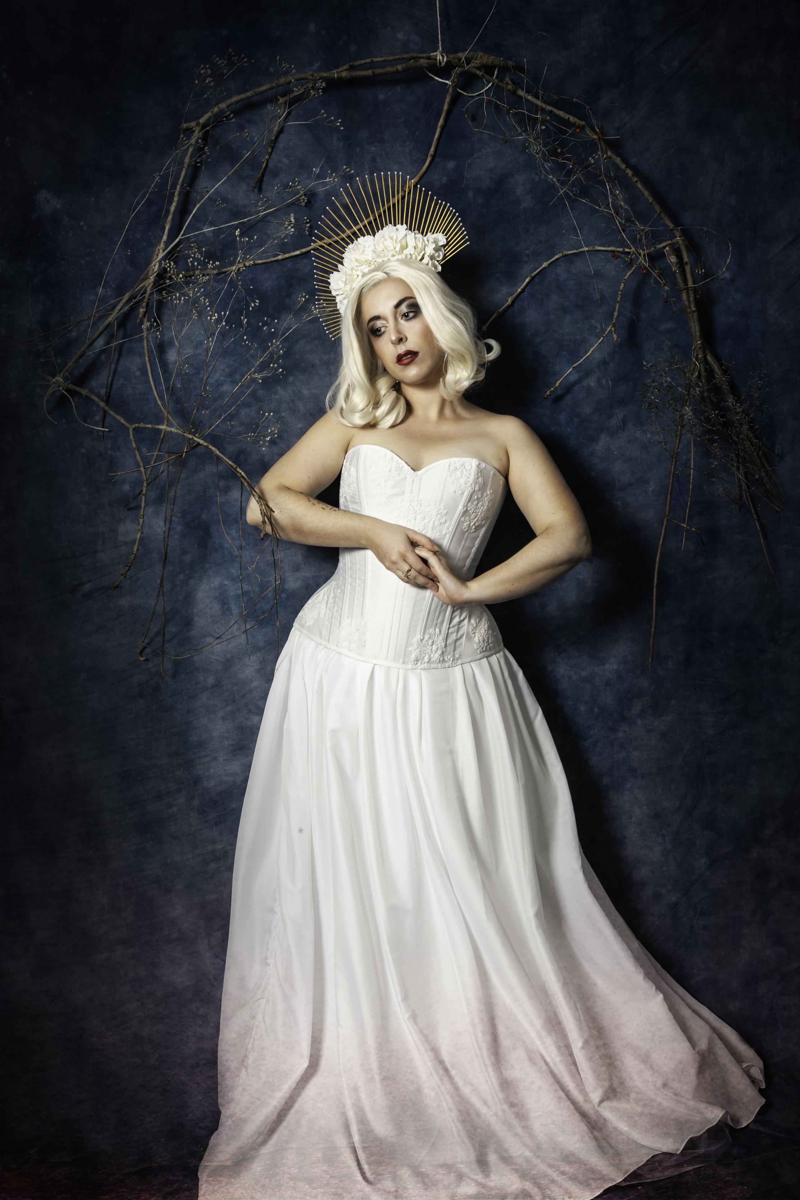 Corset blanc et dentelle, coiffe dorée, fleurs et perles blanches.